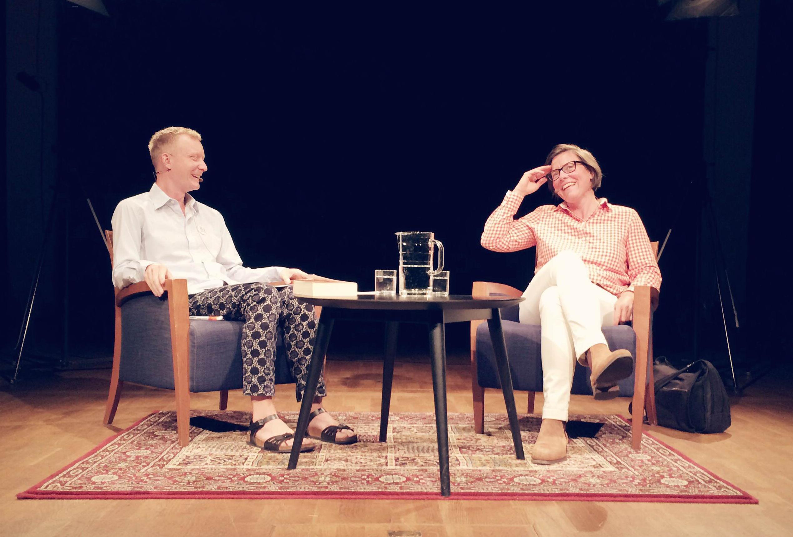 två glada personer som pratar i fåtöljer på scen