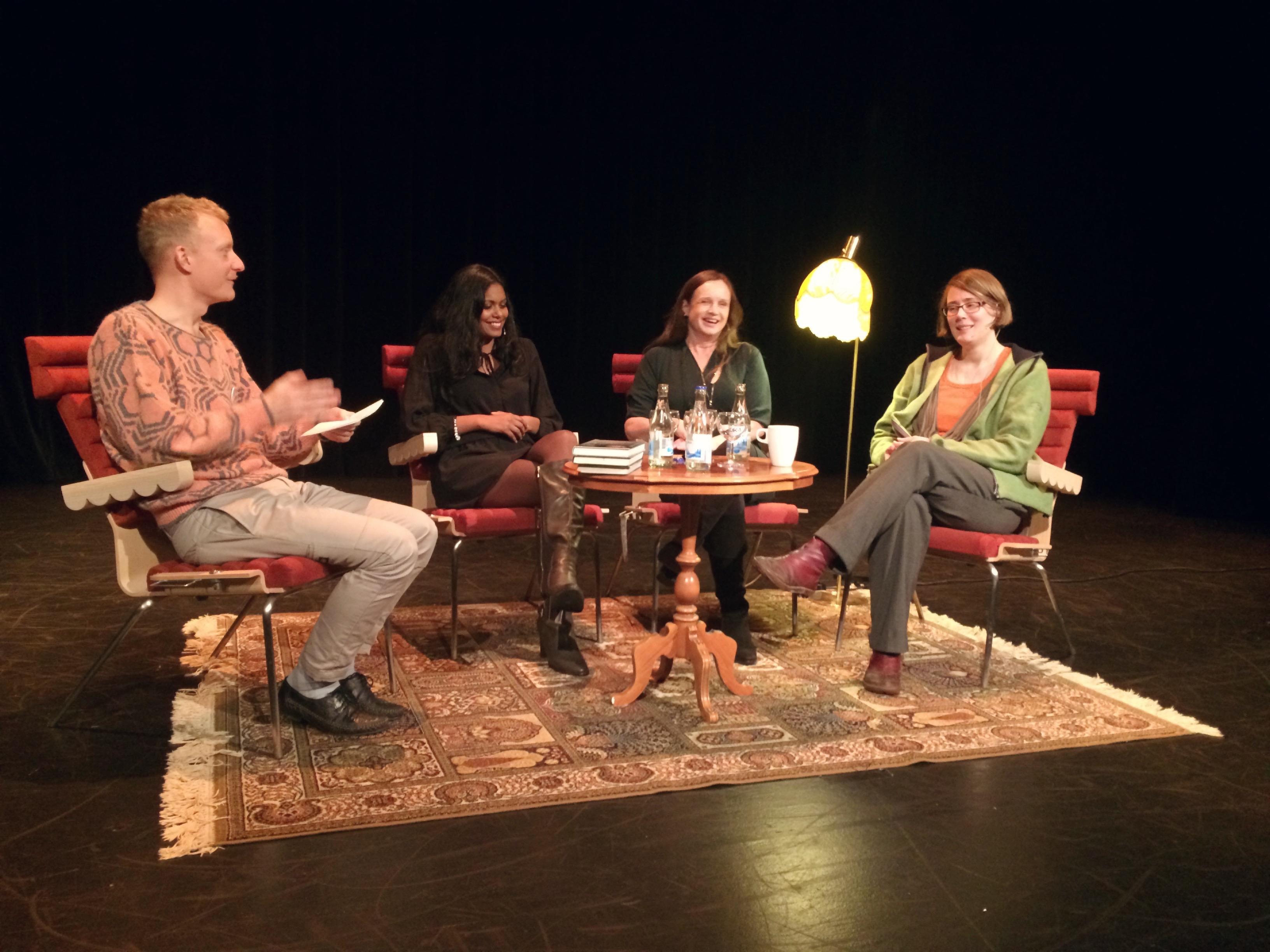 Fyra glada personer som sitter på en scen