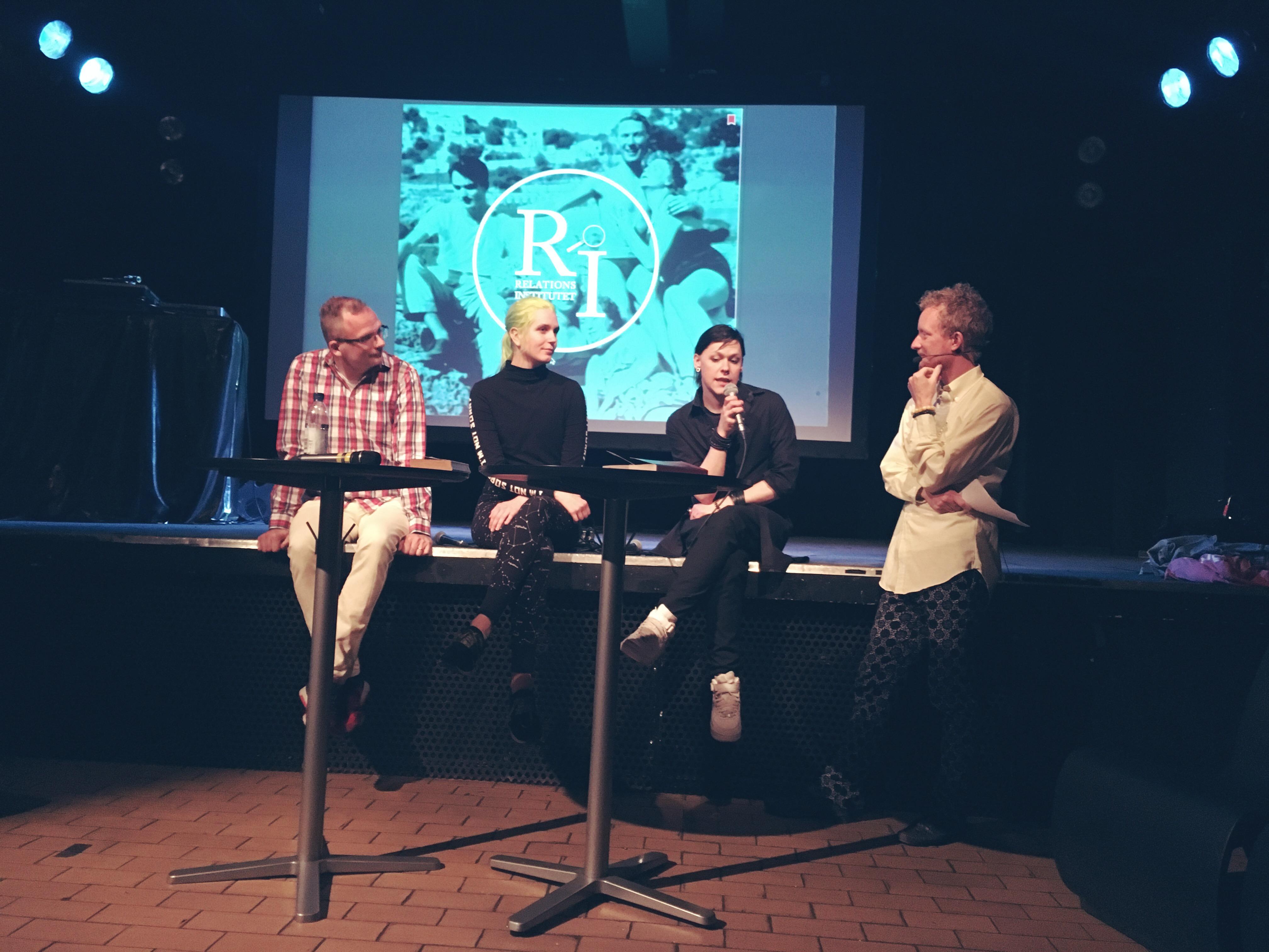 Fyra paneldeltagare på scenkanten i en mysig klubblokal